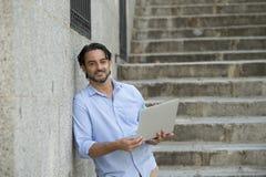 Λατινικό άτομο στη σκάλα πόλεων που λειτουργεί με το φορητό προσωπικό υπολογιστή που φαίνεται ικανοποιώ και βέβαιο Στοκ Εικόνα