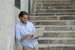 Λατινικό άτομο στη σκάλα πόλεων που λειτουργεί με το φορητό προσωπικό υπολογιστή που φαίνεται ικανοποιώ και βέβαιο Στοκ εικόνα με δικαίωμα ελεύθερης χρήσης