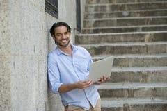 Λατινικό άτομο στη σκάλα πόλεων που λειτουργεί με το φορητό προσωπικό υπολογιστή που φαίνεται ικανοποιώ και βέβαιο Στοκ Φωτογραφίες