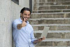 Λατινικό άτομο στη σκάλα πόλεων που λειτουργεί με το φορητό προσωπικό υπολογιστή που φαίνεται ικανοποιώ και βέβαιο Στοκ Φωτογραφία