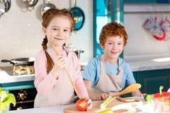 λατρευτά ευτυχή παιδιά στις ποδιές που χαμογελούν στη κάμερα μαγειρεύοντας από κοινού Στοκ Εικόνα