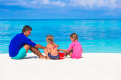 Λατρευτά κορίτσια και ευτυχές παιχνίδι πατέρων με την παραλία Στοκ φωτογραφία με δικαίωμα ελεύθερης χρήσης