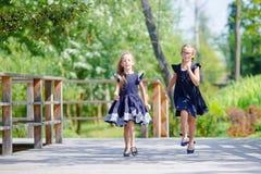 Λατρευτά κορίτσια λίγων σχολείων υπαίθρια στη θερμή ημέρα Σεπτεμβρίου πίσω σχολείο Στοκ Φωτογραφίες