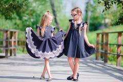 Λατρευτά κορίτσια λίγων σχολείων υπαίθρια στη θερμή ημέρα Σεπτεμβρίου πίσω σχολείο Στοκ Εικόνες