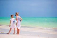 Λατρευτά μικρά κορίτσια με τις πετσέτες στην τροπική παραλία Στοκ Εικόνες