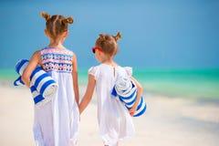 Λατρευτά μικρά κορίτσια με τις πετσέτες στην τροπική παραλία Στοκ Φωτογραφία