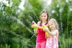 Λατρευτά μικρά κορίτσια που παίζουν με τα πυροβόλα όπλα νερού την καυτή θερινή ημέρα Χαριτωμένα παιδιά που έχουν τη διασκέδαση με Στοκ εικόνες με δικαίωμα ελεύθερης χρήσης