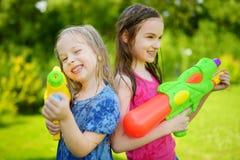 Λατρευτά μικρά κορίτσια που παίζουν με τα πυροβόλα όπλα νερού την καυτή θερινή ημέρα Χαριτωμένα παιδιά που έχουν τη διασκέδαση με Στοκ φωτογραφία με δικαίωμα ελεύθερης χρήσης