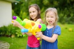 Λατρευτά μικρά κορίτσια που παίζουν με τα πυροβόλα όπλα νερού την καυτή θερινή ημέρα Χαριτωμένα παιδιά που έχουν τη διασκέδαση με Στοκ Εικόνες
