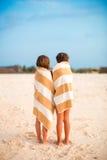 Λατρευτά μικρά κορίτσια που τυλίγονται στην πετσέτα στην τροπική παραλία Στοκ Εικόνες