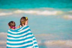 Λατρευτά μικρά κορίτσια που τυλίγονται στην πετσέτα στην τροπική παραλία Στοκ Φωτογραφίες