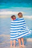 Λατρευτά μικρά κορίτσια που τυλίγονται στην πετσέτα στην τροπική παραλία Στοκ Φωτογραφία