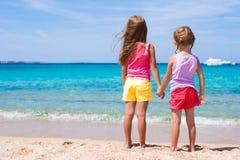 Λατρευτά μικρά κορίτσια στην τροπική παραλία κατά τη διάρκεια των θερινών διακοπών Στοκ Φωτογραφία