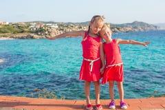Λατρευτά μικρά κορίτσια στην τροπική παραλία κατά τη διάρκεια Στοκ Φωτογραφία