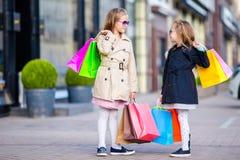 Λατρευτά μικρά κορίτσια στις αγορές Πορτρέτο των παιδιών με τις τσάντες αγορών Στοκ Εικόνες