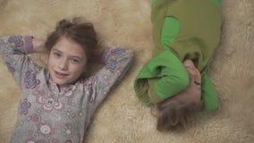 Λατρευτά μικρά παιδιά στις πυτζάμες που βρίσκονται στο πάτωμα με το χνουδωτό τάπητα αδελφή αδελφών από κοινού ευτυχείς αμφιθαλείς απόθεμα βίντεο