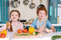 λατρευτά παιδιά που κρατούν τα ξύλινα εργαλεία και που χαμογελούν στη κάμερα μαγειρεύοντας από κοινού Στοκ Φωτογραφία
