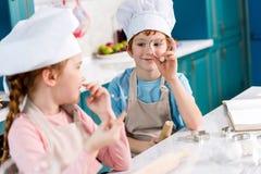 λατρευτά παιδιά στα καπέλα αρχιμαγείρων και ποδιές που χαμογελούν η μια την άλλη μαγειρεύοντας από κοινού Στοκ Φωτογραφία