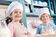 λατρευτά παιδιά στα καπέλα αρχιμαγείρων και ποδιές που χαμογελούν στη κάμερα μαγειρεύοντας από κοινού Στοκ Εικόνες