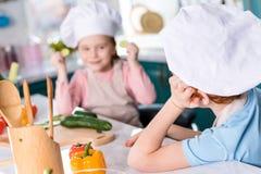 λατρευτά παιδιά στα καπέλα αρχιμαγείρων που εξετάζουν το ένα το άλλο μαγειρεύοντας από κοινού Στοκ φωτογραφία με δικαίωμα ελεύθερης χρήσης