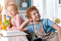 λατρευτά παιδιά στις ποδιές που χαμογελούν στη κάμερα μαγειρεύοντας με το cookbook Στοκ Εικόνες