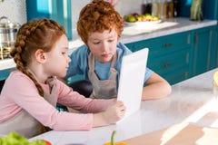 λατρευτά παιδιά στις ποδιές που χρησιμοποιούν την ψηφιακή ταμπλέτα μαγειρεύοντας από κοινού Στοκ εικόνα με δικαίωμα ελεύθερης χρήσης