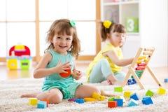 Λατρευτά παιδιά που παίζουν τα ζωηρόχρωμα παιχνίδια Στοκ φωτογραφία με δικαίωμα ελεύθερης χρήσης