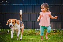 Λατρευτά τρεξίματα κοριτσάκι μαζί με το σκυλί λαγωνικών στον κήπο στη θερινή ημέρα στοκ εικόνες