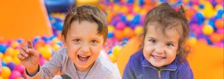 Λατρευτά χαμογελώντας μικρό κορίτσι και αγόρι Πορτρέτο Ευτυχές παιδικό παιχνίδι Στοκ Εικόνες
