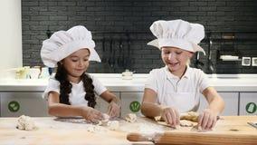 Λατρευτά schoolkids που παίζουν με τη ζύμη και το αλεύρι στην κουζίνα Οι νέοι αρχιμάγειρες εργάζονται από κοινού 4K απόθεμα βίντεο