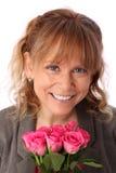 Λατρευτή γυναίκα που κρατά τα ρόδινα τριαντάφυλλα Στοκ Εικόνες