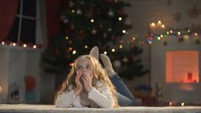 Λατρευτή επιστολή γραψίματος κοριτσιών κάτω από το καμμένος χριστουγεννιάτικο δέντρο που ονειρεύεται για το θαύμα απόθεμα βίντεο