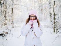 Λατρευτή ευτυχής νέα ξανθή γυναίκα στο ρόδινο πλεκτό μαντίλι καπέλων που έχει το strolling χιονώδες χειμερινό δάσος διασκέδασης σ Στοκ φωτογραφία με δικαίωμα ελεύθερης χρήσης