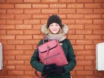 Λατρευτή ευτυχής νέα redhead γυναίκα στο πράσινο καπέλο ζακετών που έχει τη διασκέδαση στη χιονώδη χειμερινή οδό ενάντια στο τουβ Στοκ εικόνα με δικαίωμα ελεύθερης χρήσης