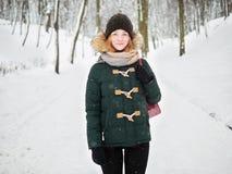 Λατρευτή ευτυχής νέα redhead γυναίκα στο πράσινο καπέλο ζακετών που έχει τη διασκέδαση στο χιονώδες χειμερινό πάρκο Στοκ Εικόνα