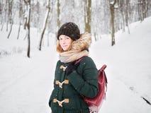 Λατρευτή ευτυχής νέα redhead γυναίκα στο πράσινο καπέλο ζακετών που έχει τη διασκέδαση στο χιονώδες χειμερινό πάρκο Στοκ Φωτογραφία