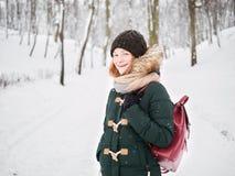 Λατρευτή ευτυχής νέα redhead γυναίκα στο πράσινο καπέλο ζακετών που έχει τη διασκέδαση στο χιονώδες χειμερινό πάρκο Στοκ Εικόνες