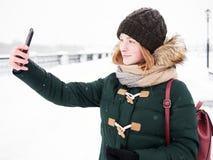 Λατρευτή ευτυχής νέα redhead γυναίκα στο πράσινο καπέλο ζακετών που έχει τη διασκέδαση στο χιονώδη χειμώνα που εξερευνά την αποβά Στοκ Φωτογραφίες