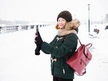 Λατρευτή ευτυχής νέα redhead γυναίκα στο πράσινο καπέλο ζακετών που έχει τη διασκέδαση στο χιονώδη χειμώνα που εξερευνά την αποβά Στοκ φωτογραφία με δικαίωμα ελεύθερης χρήσης