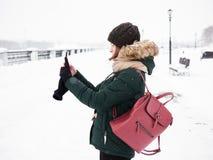 Λατρευτή ευτυχής νέα redhead γυναίκα στο πράσινο καπέλο ζακετών που έχει τη διασκέδαση στο χιονώδη χειμώνα που εξερευνά την αποβά Στοκ εικόνα με δικαίωμα ελεύθερης χρήσης