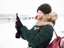 Λατρευτή ευτυχής νέα redhead γυναίκα στο πράσινο καπέλο ζακετών που έχει τη διασκέδαση στο χιονώδη χειμώνα που εξερευνά την αποβά Στοκ Φωτογραφία