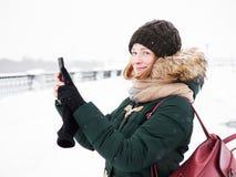 Λατρευτή ευτυχής νέα redhead γυναίκα στο πράσινο καπέλο ζακετών που έχει τη διασκέδαση στο χιονώδη χειμώνα που εξερευνά την αποβά Στοκ φωτογραφίες με δικαίωμα ελεύθερης χρήσης