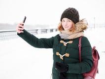 Λατρευτή ευτυχής νέα redhead γυναίκα στο πράσινο καπέλο ζακετών που έχει τη διασκέδαση στο χιονώδη χειμώνα που εξερευνά την αποβά Στοκ Εικόνες