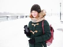 Λατρευτή ευτυχής νέα redhead γυναίκα στο πράσινο καπέλο ζακετών που έχει τη διασκέδαση στο χιονώδη χειμώνα που εξερευνά την αποβά Στοκ Εικόνα