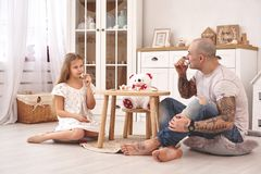 Λατρευτή κόρη που φορά ένα άσπρο φόρεμα whith ο αγαπώντας πατέρας της Πίνουν το τσάι από τα πιάτα παιχνιδιών σε ένα σύγχρονο παιδ στοκ εικόνα