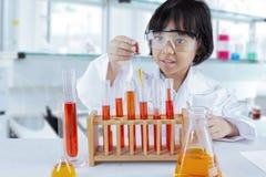 Λατρευτή μαθήτρια που αναμιγνύει το χημικό υγρό στοκ εικόνα