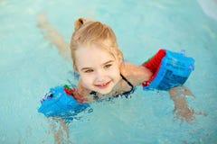 Λατρευτή ξανθή κολύμβηση μικρών κοριτσιών στη λίμνη με armbands α Στοκ εικόνες με δικαίωμα ελεύθερης χρήσης