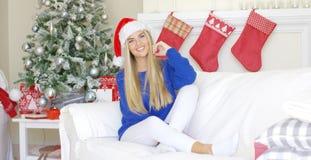 Λατρευτή ξανθή συνεδρίαση κοριτσιών στον καναπέ στο καπέλο Άγιου Βασίλη Στοκ Εικόνες