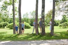 Λατρευτή οικογένεια πίσω από τα δέντρα στοκ φωτογραφίες