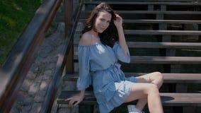 Λατρευτή συνεδρίαση γυναικών brunette στα σκαλοπάτια σε υπαίθριο φιλμ μικρού μήκους